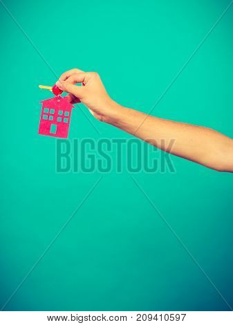 Household savings housekeeping real estate concept. Person holding keys with small pendant in the shape of a house studio shot on blue background