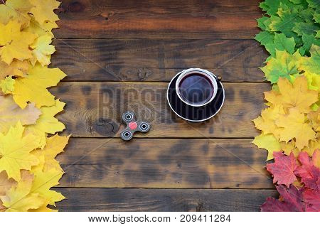 A Cup Of Tea And A Wooden Spinner Among The Many Yellowing Fallen Autumn Leaves On The Background Su