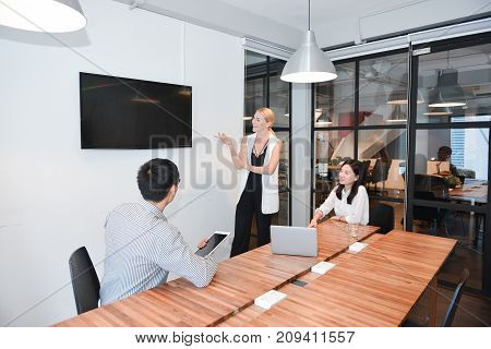 Business Blonde Woman And Colleagues Watching Tv With Blank Screen In Office, Multi Ethnic