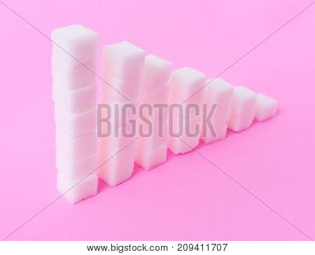 High to low stacks of sugar cubes with pink background health care diet concept