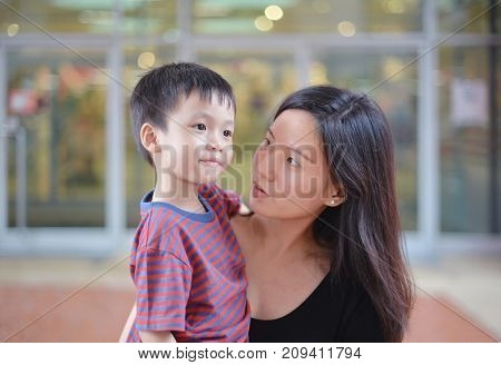 Young Asian Mother And Her Kid Looking At Each Other