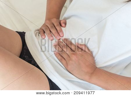 Closeup woman hand holding abdominal with stomach ache lying on bed health care and medical concept
