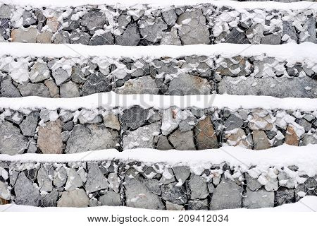 Gray stone wall in winter snow rows background