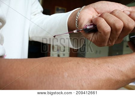 Men using a injection needles and blood in the syringe.