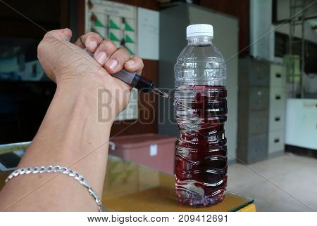 Men use a syringe to inject blood in the drinking water.