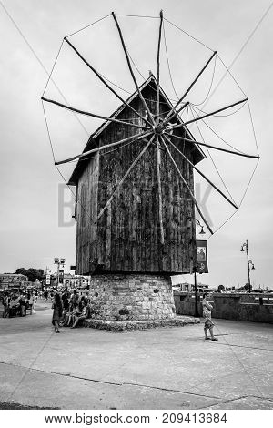 NESEBAR BULGARIA - AUGUST 21 2017: An old wooden windmill on the embankment in the old town. Black and white. Nesebar is an ancient city and one of the major seaside resorts on the Bulgarian Black Sea Coast.