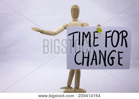 A yellow sticky note post it writing, caption, inscription Time For Change in black ext on a sticky note pinned to board