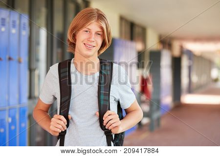 Happy white teenage boy smiling in high school corridor