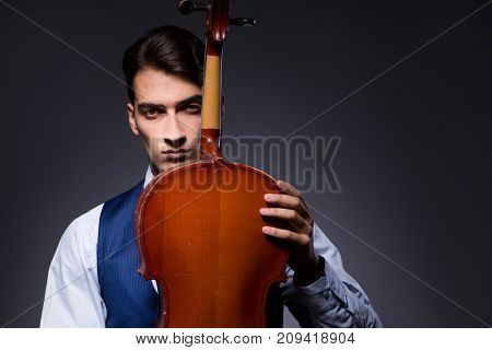 Young man playing cello in dark room