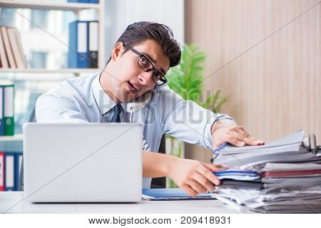 Businessman with excessive work paperwork working in office
