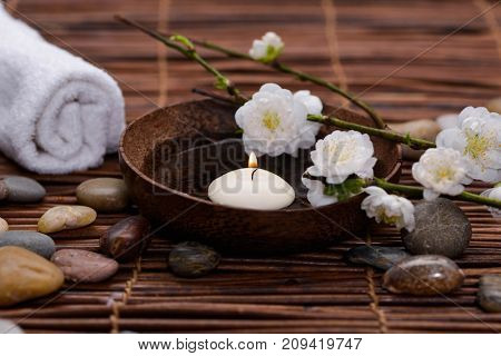 Lying white cherry,candle ,in wooden bowl with stones, rolled towel and mat