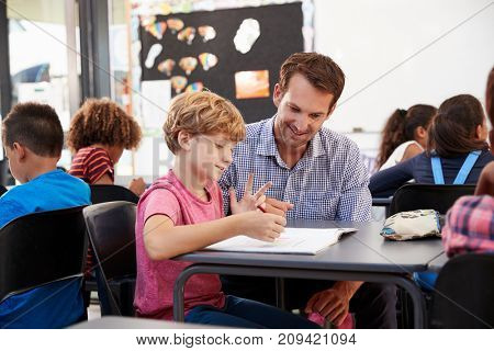 Teacher and young school boy looking at notebook in class