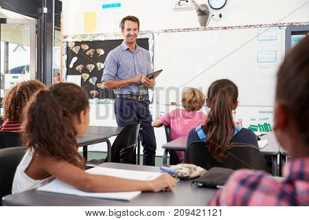 Teacher with tablet in front of elementary school class