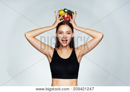 a young slender girl eats only healthy healthy food, holds a plate with apples above her head