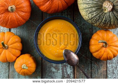 Healthy vegan pumpkin puree with sesame seeds decorated with orange and green pumpkins on rustic blue background above view overhead view