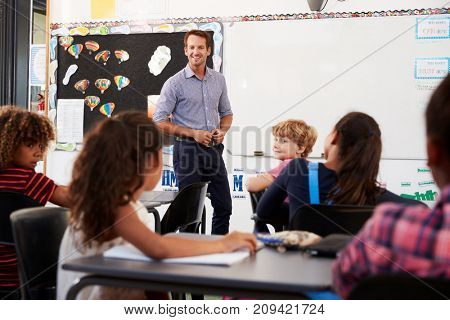 Smiling teacher at front of elementary school class