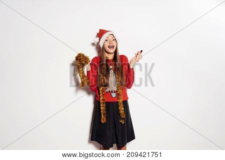 laughing young long-haired girl has fun for the new year, and Christmas, with a golden festive tinsel and a red cap on her head