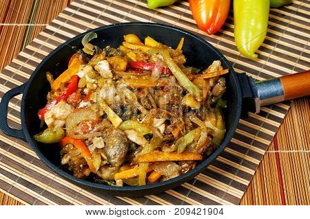 Stewed chicken with vegetables in cast iron cookware