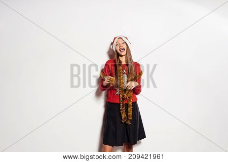 happy young girl celebrates the new year in a festive sweater and gold tinsel on the neck