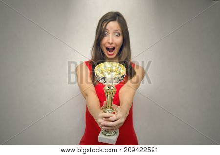 VIP client. Premium user concept. Success. Young woman in red dress holding in hands golden cup trophy in front of herself and admires with open mouth. Award ceremony. First place in pageant.