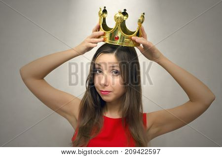 Young beautiful woman in red dress with golden crown above her head. VIP client. Premium user concept. Success. Award ceremony. Beauty contest. First place in pageant.