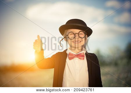Outdoor portrait of funny little girl in bow tie and bowler hat showing thumb up. Retro stile.