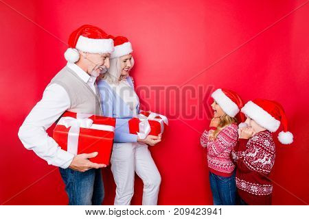 Four relatives: married senior couple of grandad and granny in knitted cute traditional x mas outfits prepard surprises for cheerful siblings full of emotions isolated on the red background