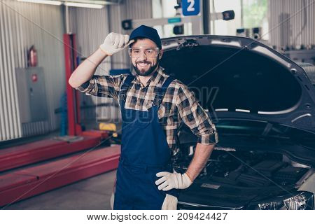 Attractive Caucasian Expert Assistant At Mechanical Work Shop, Standing, Fixing Headwear, In Special