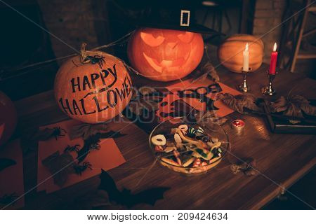 High angle shot of cutted pumpkin fall leaves spider web net skull cap of witch bowl with sweets on top of wooden table. Ready for feast in mystery interior. Concept of hallows eve