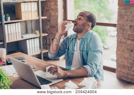 Young Ill Afro Student Is Sneezing At Work Place In Modern Office, A Lot Of Paper  Napkins On Deskto
