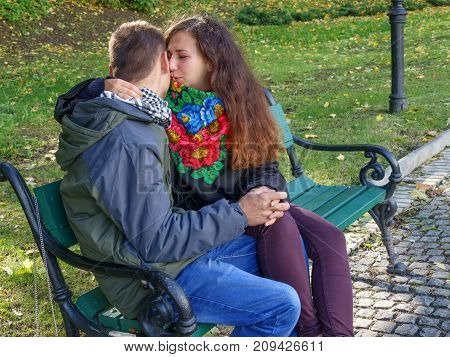Enamored guy and girl on a date talking on a bench in an autumn park