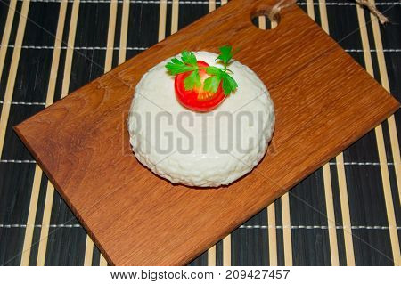 Young oak cheese cutting Board with tomatoes and parsley. Mozarella for pizzas and salads.
