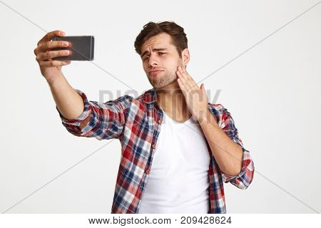 Portrait of a handsome confident man taking a selfie while standing and posing isolated over white background