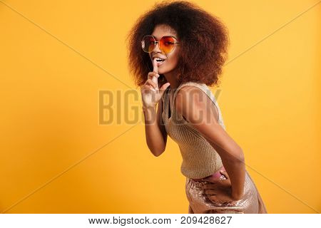 Portrait of a smiling afro american woman dressed in retro clothes posing while showing silence gesture over her lips isolated over yellow background