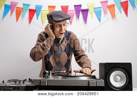 Elderly DJ playing music on a turntable against a wall with decoration flags