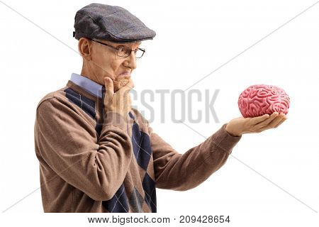 Pensive senior looking at a brain model isolated on white background