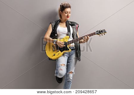 Female punker leaning against a gray wall and playing an electric guitar