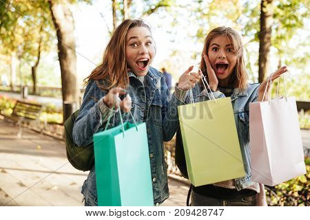 Portrait of two happy excited girls holding shopping bags and screaming on a city street