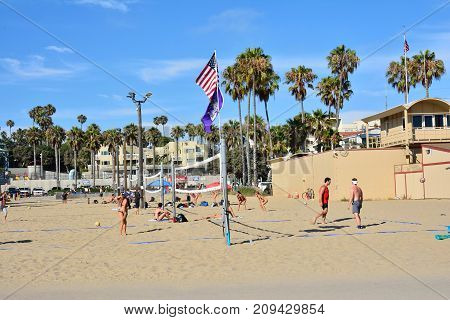 People Are Playing Beach Volleyball At Santa Monica.