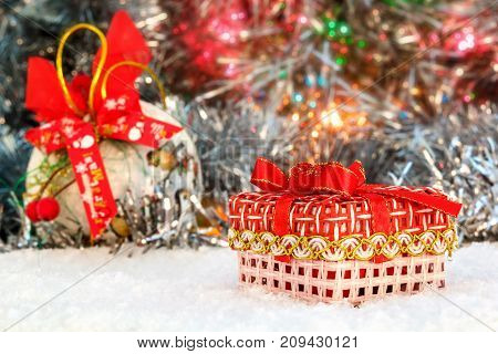 red Christmas present stands on the snow against a background of a Christmas ball and shiny tinsel. glowing lights. bokeh. Christmas and New Year. place for text