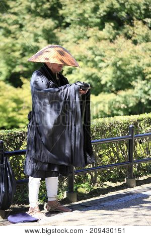 Kyoto City, Japan - Oct 6, 2010: A monk is begging alms in the trail where many tourists walk along.