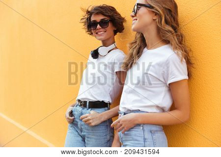 Two smiling young teenage girls pin sunglasses posing outdoors while leaning on an orange wall