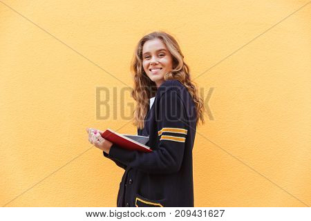 Pretty smiling teenage girl holding book and looking at camera over orange wall background