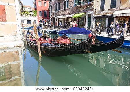 VENICE ITALY-SEPTEMBER 22 2017: Gondola - symbol of Venice narrow side channel. Gondola is iconic traditional boat very popular means of transport for tourists