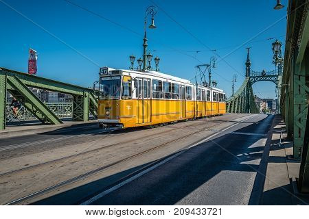 Budapest, Hungary - August 14, 2017:  Liberty Bridge in Budapest. Yellow tram crossing the bridge. It connects Buda and Pest across the River Danube. Sunny day of summer