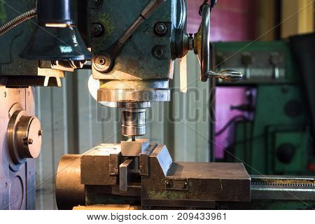 Mechanical vertical milling machine. The parts clamped in the machine vice are ready for processing.