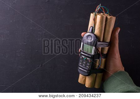 Bomb with explosives and detonator phone in the hands of a terrorist. The denamite sticks are connected by wires with a phonemon. Black background. Copy space for text