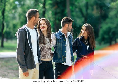 Four Carefree Young People Walking In Park On Sunny Day