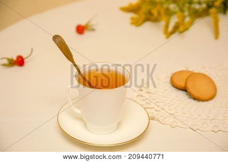 Cup of tea with pastries on linen tablecloth