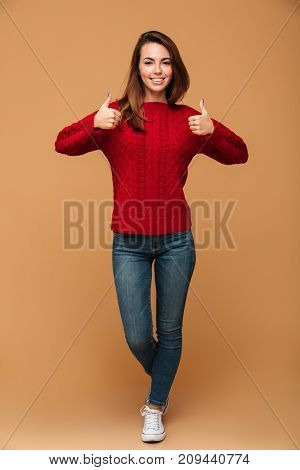 Full length portrait of smiling brunette woman in red knitted sweater and jeans showing thumbs up gesture with two hands, looking at camera, isolated on beige background